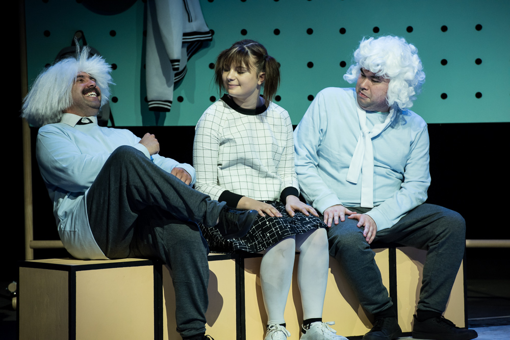 A photo of two men in white wigs sitting either side of a woman in pigtails. One man is laughing.
