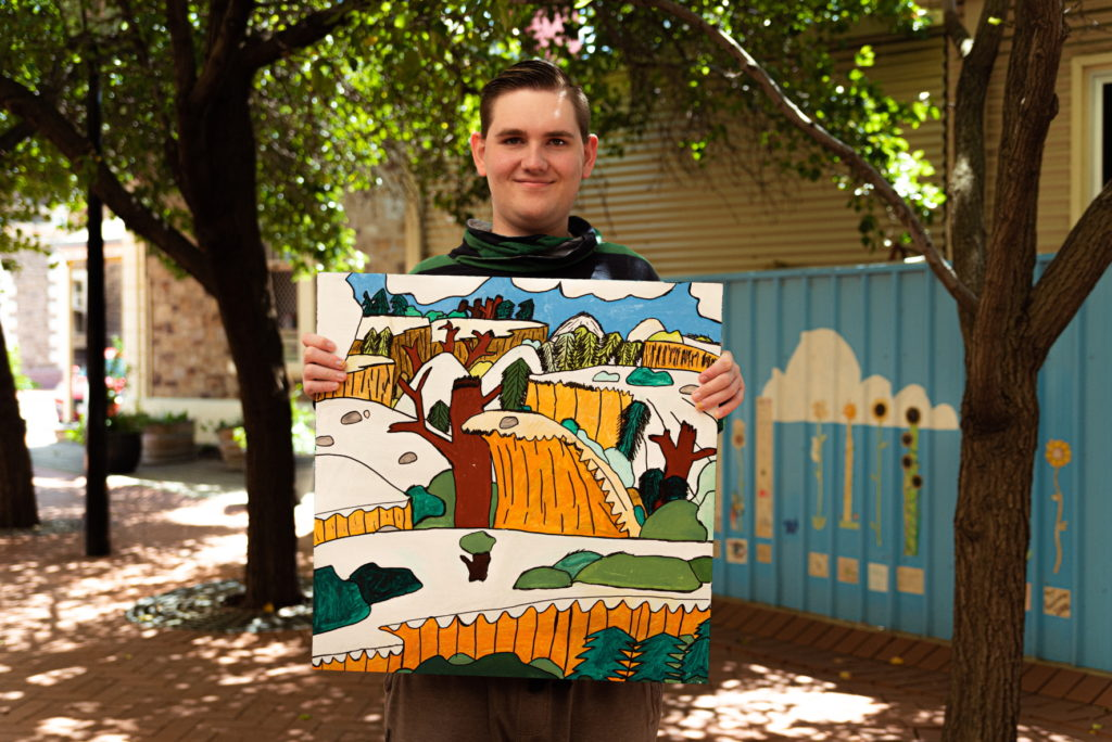 A photo of a man standing outside, holding an artwork with an animation aesthetic